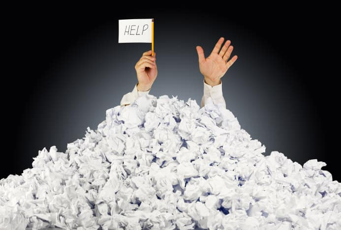 This image of two hands emerging from a pile of papers epitomizes needing help and being overwhelmed.
